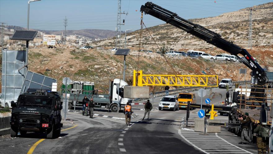 Israelíes colocan un bloque de hormigón en una carretera en la Cisjordania para separar a los conductores israelíes de los palestinos, 10 de enero de 2019. (Foto: AFP)