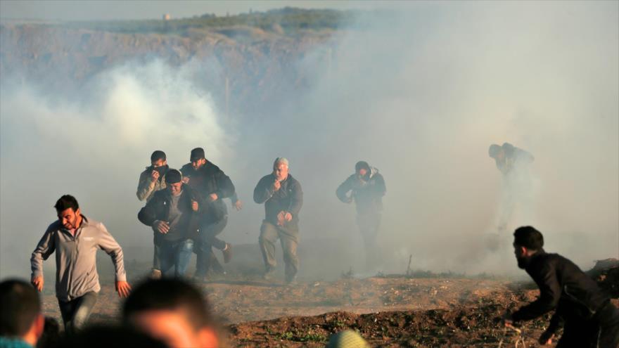 Manifestantes palestinos atraviesan humos de gas lacrimógeno disparados por militares israelíes al este de Gaza, 11 de enero de 2019. (Foto: AFP)