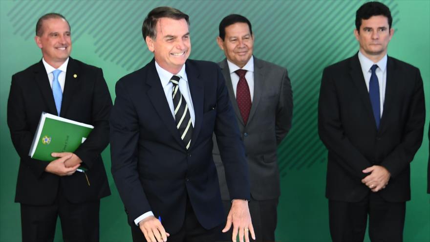 El presidente brasileño, Jair Bolsonaro, firma un decreto que permite el porte de armas de fuego, Brasilia, 15 de enero de 2019. (Foto: AFP)