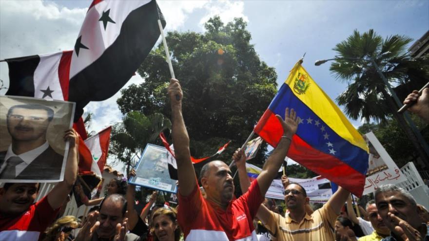 Un grupo de manifestantes ondean banderas sirias y venezolanas frente a la embajada de Siria en Caracas.