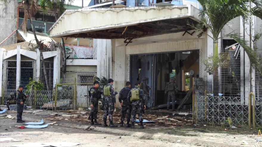 Militares filipinos en las afueras de una iglesia en Joló (sur), donde el grupo EIIL realizó un doble atentado, 27 de enero de 2019. (Foto: AFP)