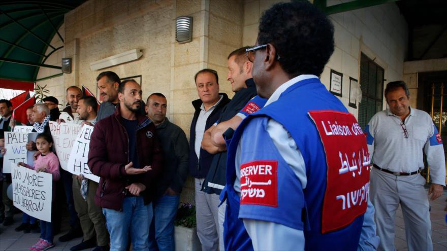 Observadores de la TIPH en Al-Jalil, junto a un grupo de palestinos en la ciudad ocupada de Cisjordania, 30 de enero de 2019. (Foto: AFP)