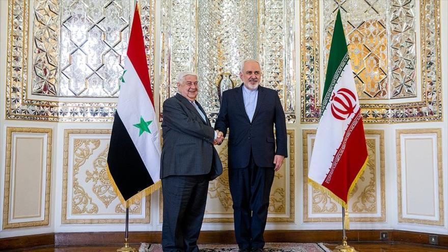 El canciller de Irán, Mohamad Yavad Zarif (dcha.) se reúne con su par sirio, Walid al-Moalem, en Teherán, la capital iraní, 5 de febrero de 2019.