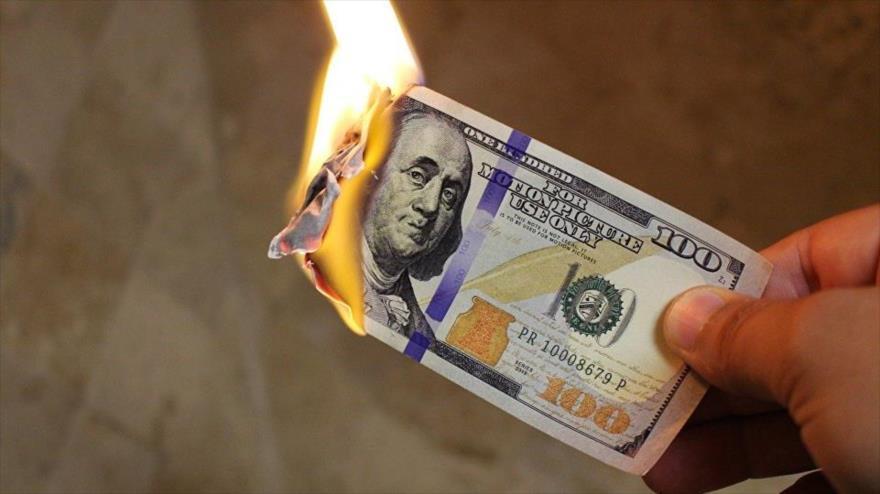 Un billete de 100 dólares estadounidenses en llamas.
