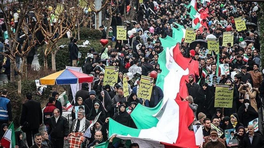 Ciudadanos iraníes portan una gran bandera nacional en la marcha por la victoria de la Revolución Islámica en Teherán, capital persa, 11 de febrero de 2019.