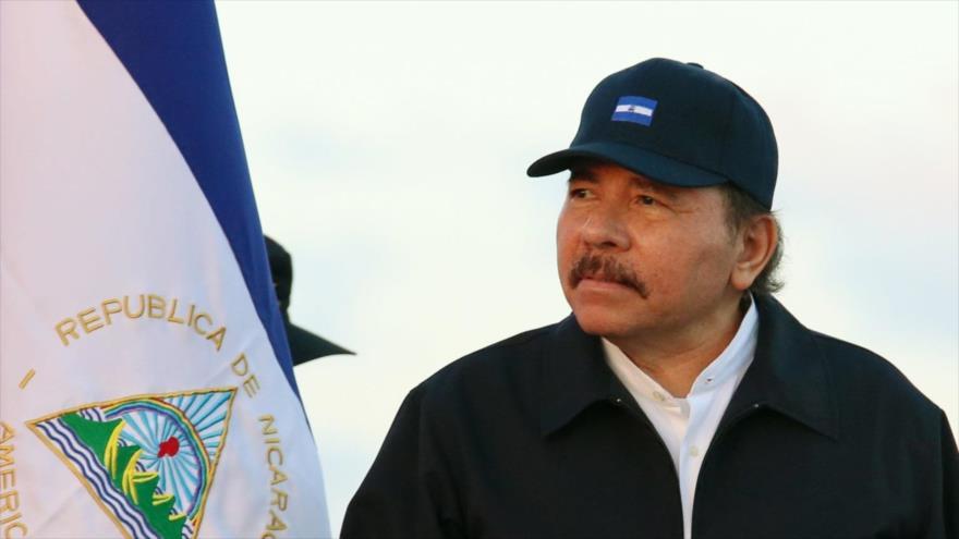 El presidente de Nicaragua, Daniel Ortega, junto a la bandera nacional del país centroamericano.