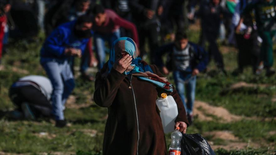 Mujer palestina se cubre la cara del humo de gas lacrimógeno lanzado por las fuerzas israelíes, este de la ciudad de Gaza, 8 de marzo de 2019. (Foto: AFP)