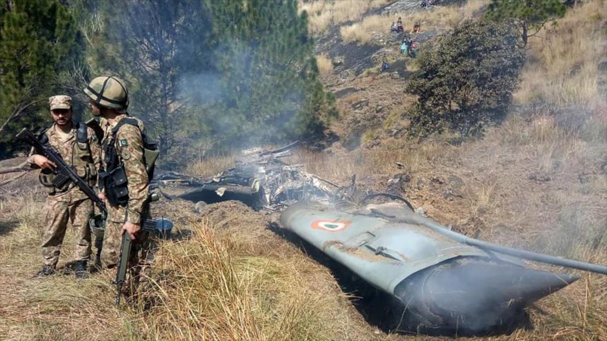 Los soldados paquistaníes junto a los restos de un avión de combate indio derribado en la Cachemira controlada por Paquistán, 27 de febrero de 2019. (Foto: AFP)