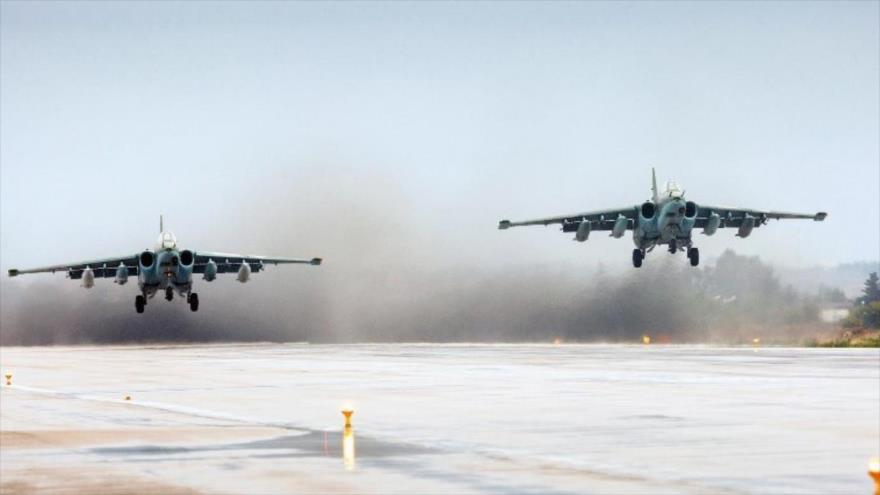 Dos cazas rusos Su-25 despegando de la base aérea de Hmeimim en Siria.