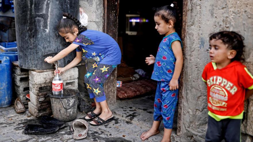 Una niña palestina llena una botella con agua en el sur de la Franja de Gaza, 24 de octubre de 2018. (Foto: AFP)
