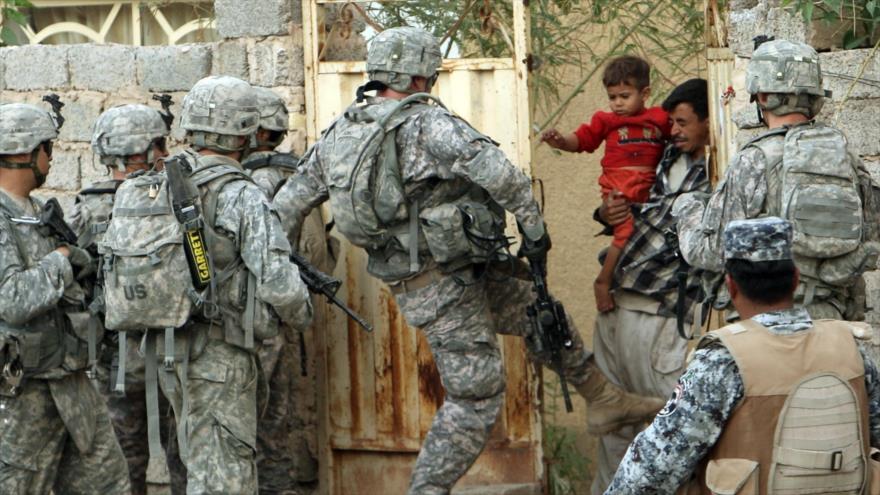 Soldados estadounidenses tratan de allanar una vivienda familiar en Irak.