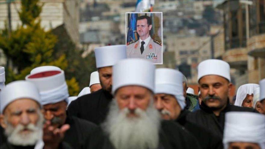 Los residentes drusos de los altos del Golán llevan un retrato del presidente sirio durante un mitin en la aldea de Majdal Shams, 14 de febrero de 2019.