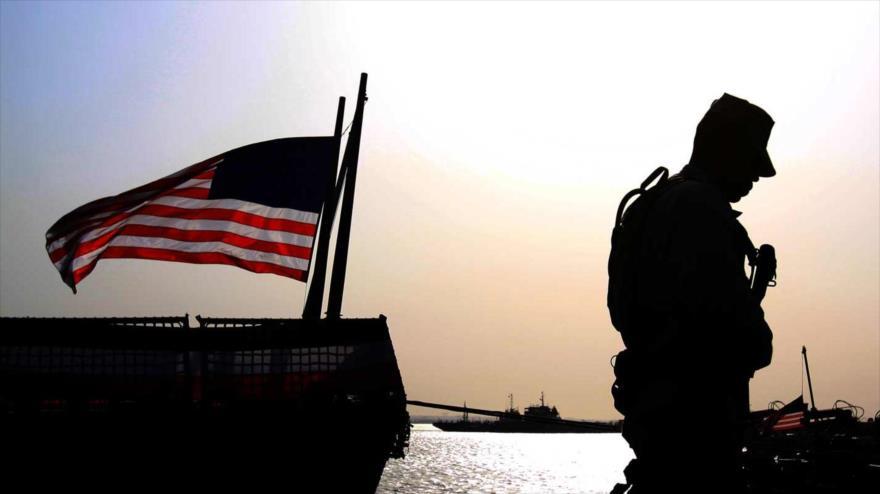 Un soldado estadounidense patrulla al lado de la bandera de EE.UU en un barco militar atracado en Manama, Baréin. (Foto: AP)