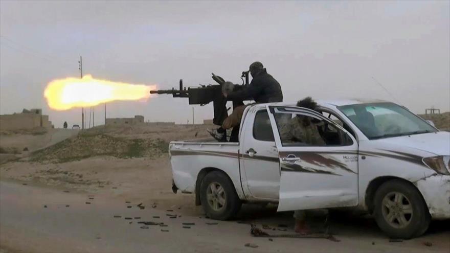 Un terrorista EIIL dispara contra las posiciones de milicias kurdo-sirias en la provincia oriental siria de Deir Ezzor, 18 de enero de 2019. (Foto: AP)