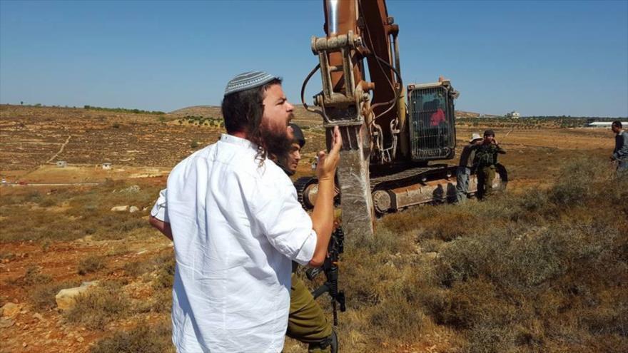 Un colono judío y un grupo de soldados israelíes, se encuentran en terrenos de los palestinos en la ocupada Cisjordania.