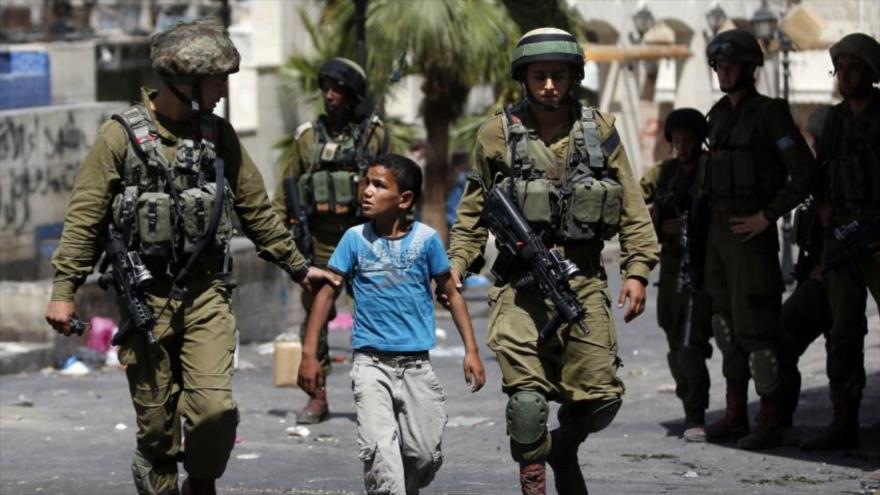 Fuerzas israelíes arrestan a un menor palestino.