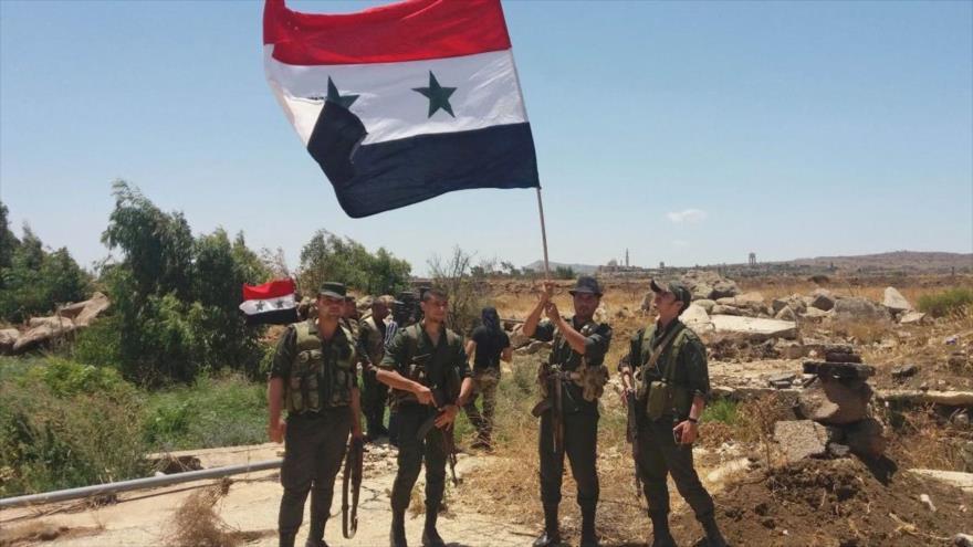 Soldados del Ejército sirio portan la bandera nacional en el pueblo de Al-Hamidiya, en la provincia suroccidental de Al-Quneitra, 26 de julio de 2018.