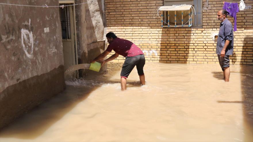 Iraníes vacían a cubos el agua de una casa en la ciudad de Hamidie, en la provincia de Juzestán (suroeste de Irán) afectada por las inundaciones, 10 de abril de 2019. (Foto: AFP)