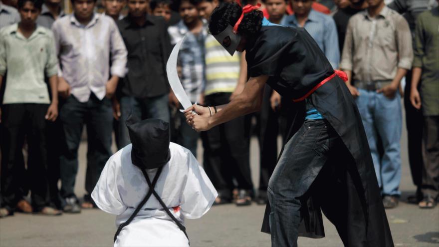 Manifestantes contra la decapitación de trabajadores extranjeros en Arabia Saudí organizan una simulación de decapitación.