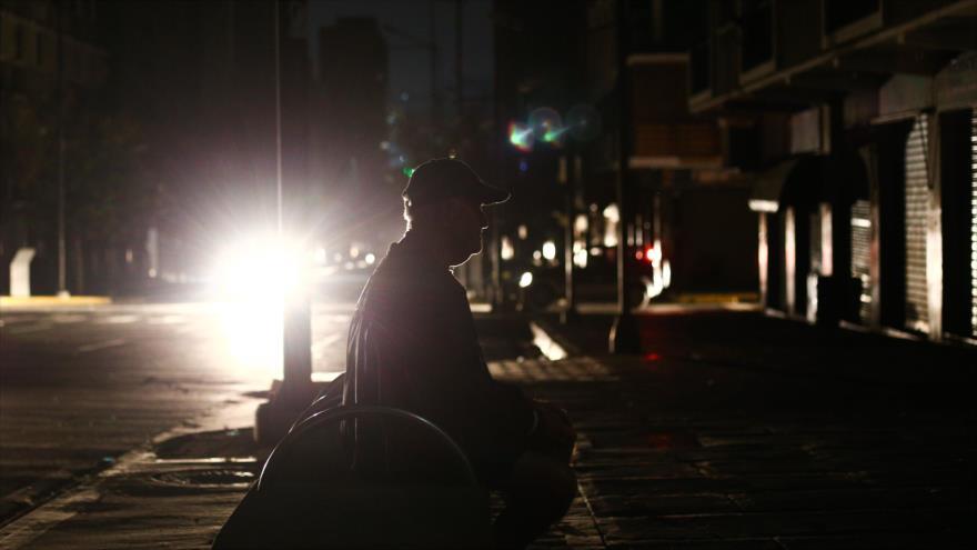 Un hombre se sienta en un banco a oscuras, durante un corte de energía en Caracas, capital de Venezuela, 27 de marzo de 2019. (Foto: AFP)