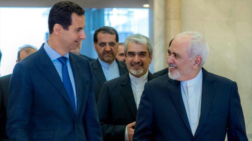 El presidente sirio, Bashar al-Asad (izq.), recibe al canciller iraní, Mohamad Yavad Zarif, en Damasco, la capital siria, 16 de abril de 2019.
