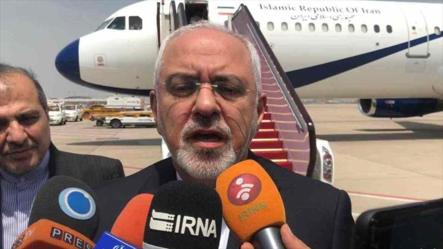 El canciller iraní, Mohamad Yavad Zarif, habla con los periodistas en un viaje al extranjero.