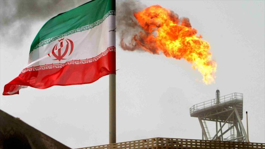 Una bandera nacional iraní, junto a una llama de gas en una plataforma de producción de petróleo.