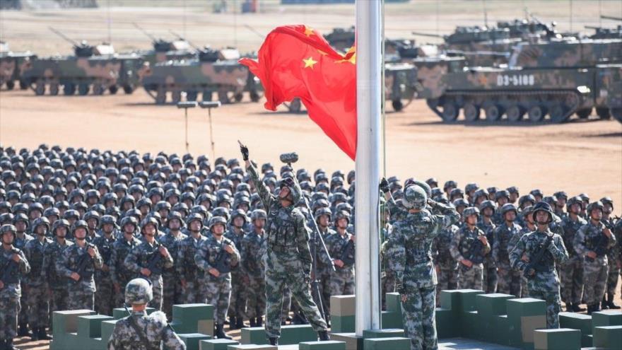 Militares chinos enarbolan su bandera en una maniobra militar.