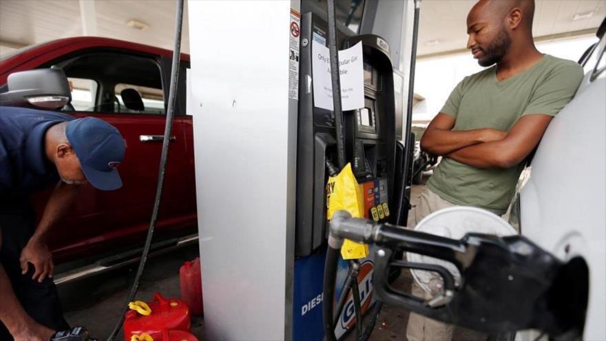 Un consumidor estadounidense espera mientras carga el tanque de gasolina de su vehículo en una estación de repostaje en EE.UU.