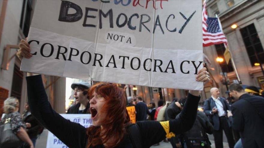 Una mujer protesta en EE.UU. portando una pancarta que exige democracia.