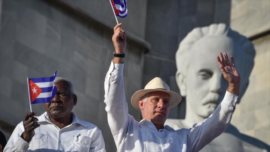 El presidente cubano, Miguel Díaz-Canel (dcha.) sostiene bandera cubana durante un mitin en La Habana, 1 de mayo de 2019. (Foto: AFP)