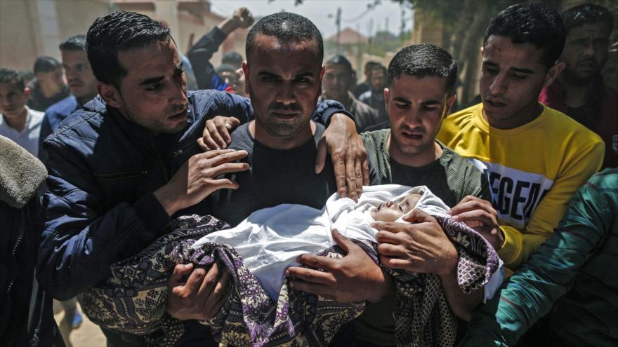 Varios palestinos portan el cuerpo sin vida de un bebé asesinado en un ataque israelí contra Gaza, 5 de mayo de 2019. (Foto: AFP)