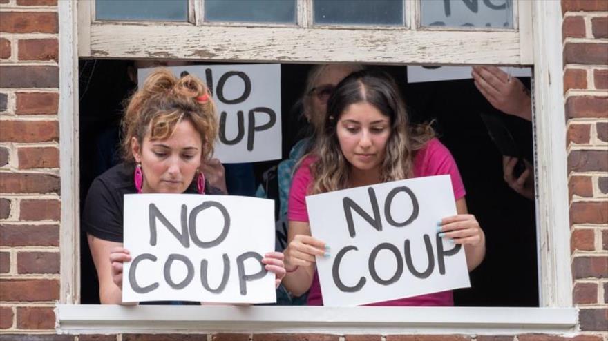 Activistas de la organización Code Pink muestran carteles desde una de las ventanas de la Embajada de Venezuela en EE.UU., 9 de mayo de 2019. (Foto: codepink.org)