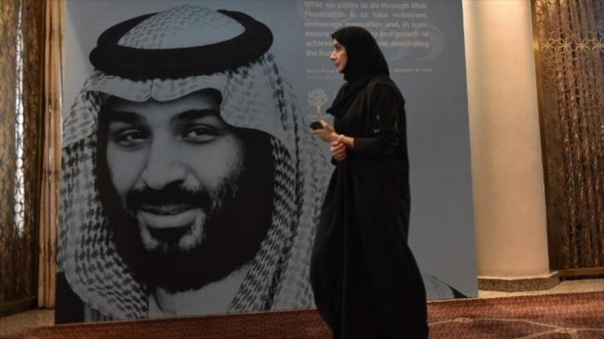 Una mujer pasa al lado de imagen del príncipe heredero de Arabia Saudí, Muhamad bin Salman.