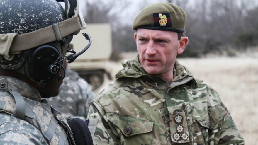 Christopher Ghika, comandante adjunto británico de la llamada coalición anti-EIIL, habla con un soldado de EE.UU., 24 de febrero de 2014.