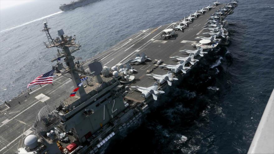 El portaviones USS Abraham Lincoln navega en las aguas del Mar Arábigo cerca del buque anfibio de asalto USS Kearsarge,17 de mayo de 2019.