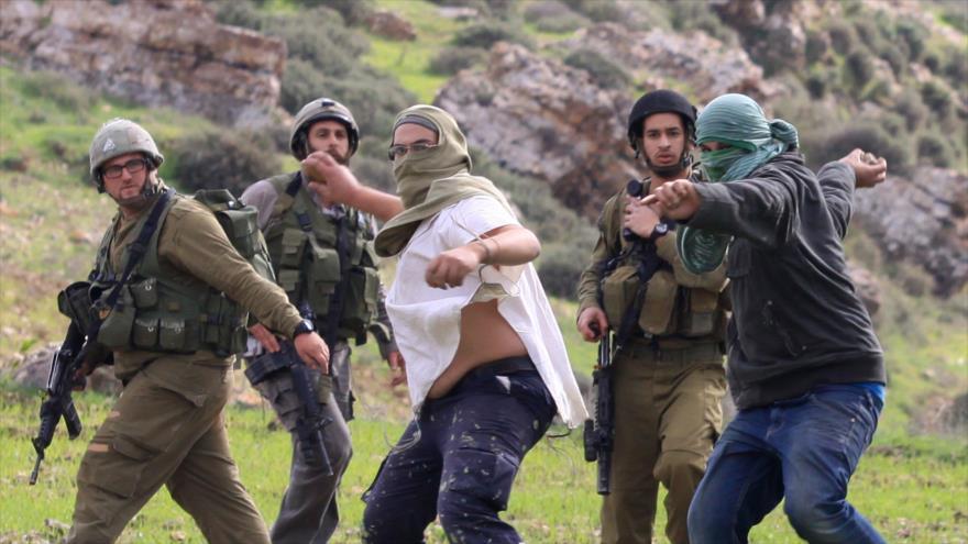 Colonos atacan a los palestinos delante de los soldados israelíes