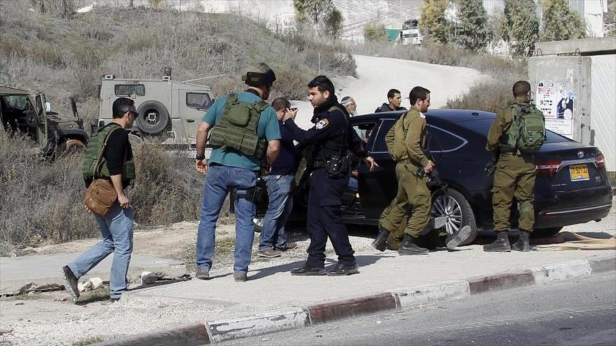 Soldados israelíes inspeccionan el coche de un colono que atropelló a un palestino cerca de la ciudad cisjordana de Nablus.