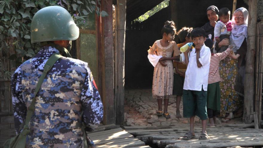 Agente de seguridad birmano vigilan a rohingyas en la localidad de Buthidaung, estado de Rajine, 25 de enero de 2019. (Foto: AFP)