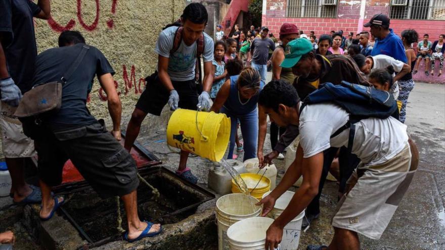 Un grupo de venezolanos rellenan sus cubos de agua.