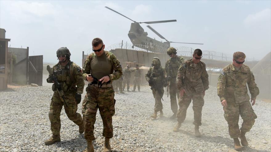 Soldados del Ejército de EE.UU. caminan mientras un helicóptero de la OTAN sobrevuela una base en Nangarhar (Afganistán), agosto de 2015. (Foto: AFP)