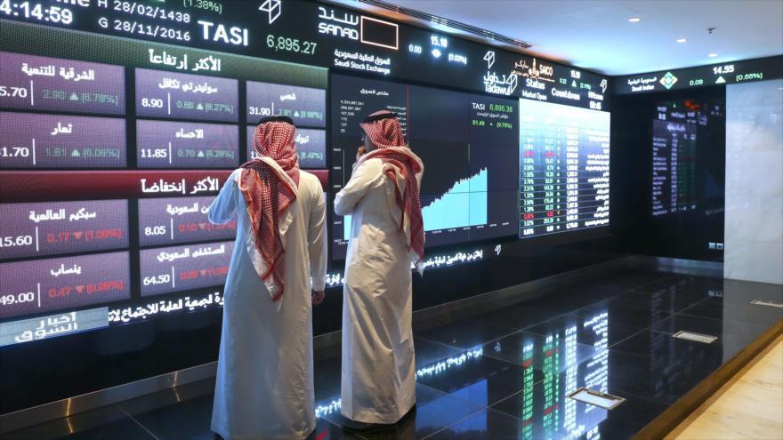 Dos inversionista saudíes frente a los monitores de la bolsa de valores de Arabia Saudí, en Riad (capital saudí).