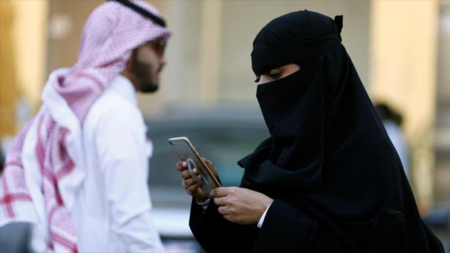 Una mujer saudí usa su teléfono móvil en calle.