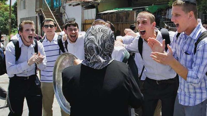 Colonos israelíes acosan a una mujer palestina en la ciudad de Al-Quds (Jerusalén).