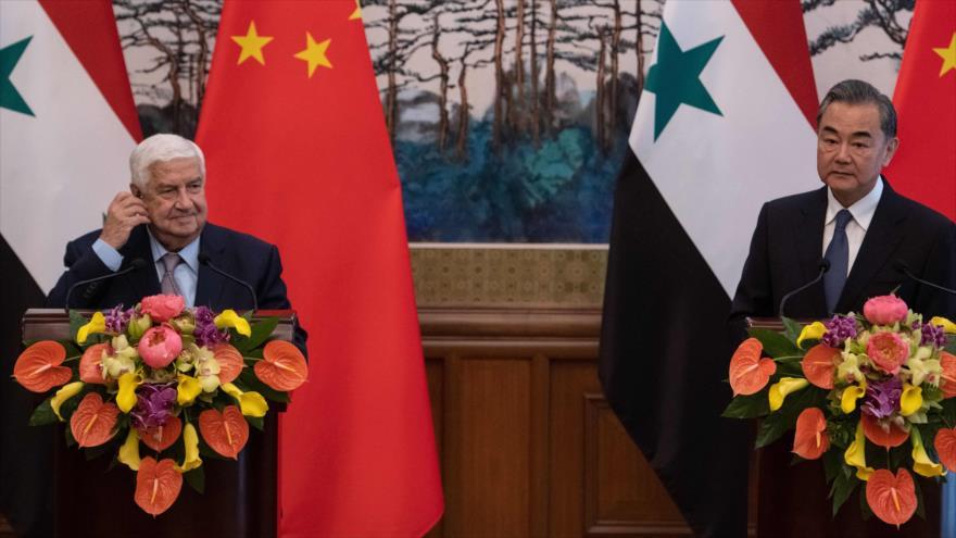El canciller de Siria, Walid al-Moalem (izq.), en una rueda de prensa con su par chino, Wang Yi, celebrada en Pekín, 18 de junio de 2019. (Foto: AFP)
