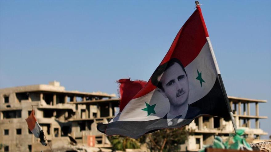 Una bandera siria con una foto del presidente, Bashar al-Asad, en la ciudad de Duma, cerca de Damasco, 15 de julio de 2018. (Foto: AP)