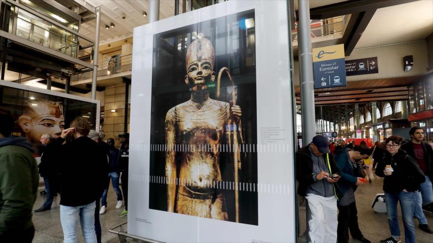 La gente se para al lado de las imágenes de la exposición Tutankamón, el Tesoro del Faraón, celebrada en París, Francia, 12 de junio de 2019. (Foto: AFP)