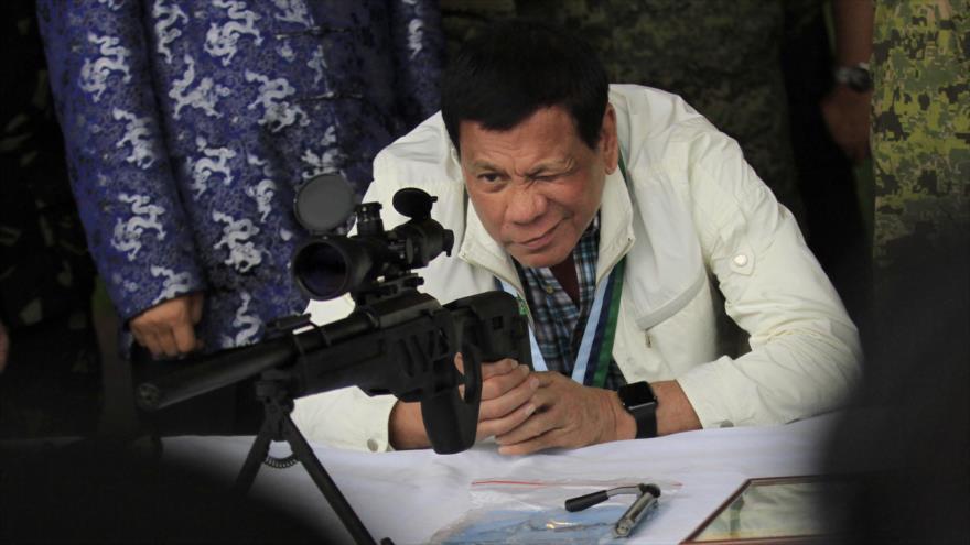 El presidente filipino, Rodrigo Duterte, examina la mira de un rifle para francotiradores CS/LR4A, de manufactura china.