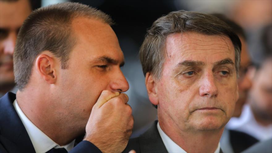 Jair Bolsonaro (dcha.), presidente de Brasil, escucha a su hijo Eduardo en un acto en la sede del Gobierno, 14 de noviembre de 2018. (Foto: AFP)