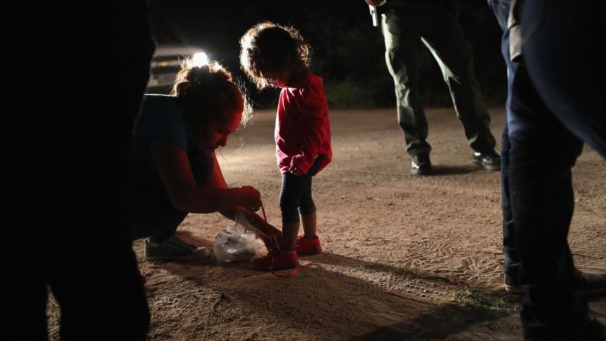 Una madre hondureña le quita los cordones de los zapatos a su hija de 2 años en la frontera con EE.UU.